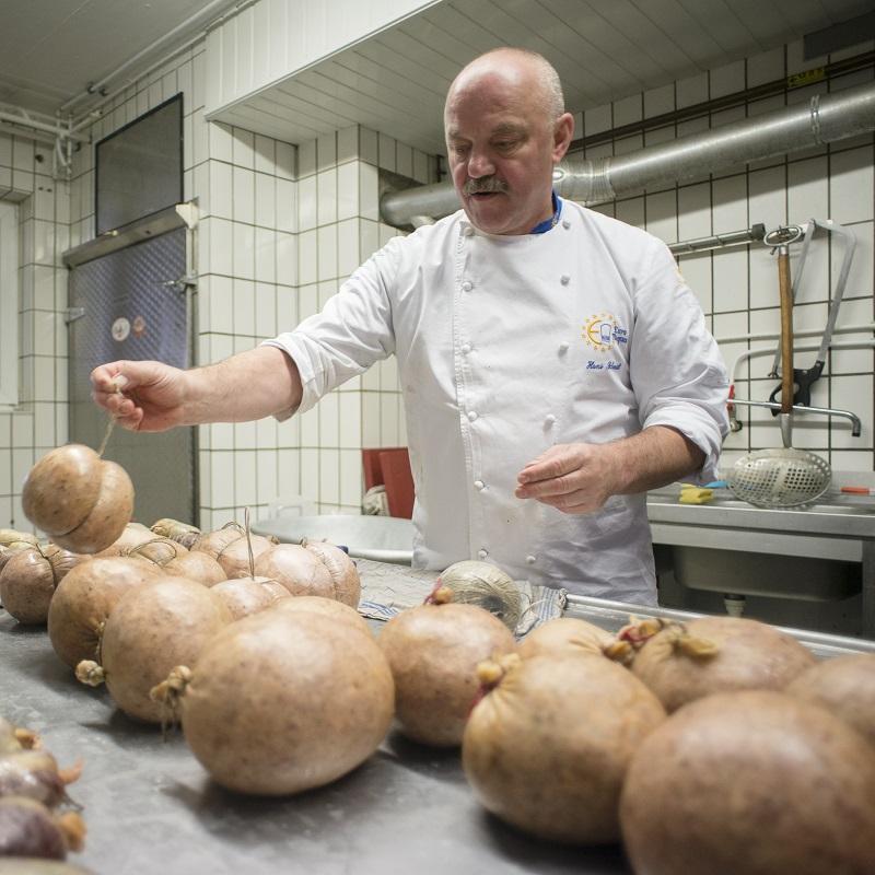 Hans Schmidt in der Wurstküche bei der Herstellung von Schwartenmagen
